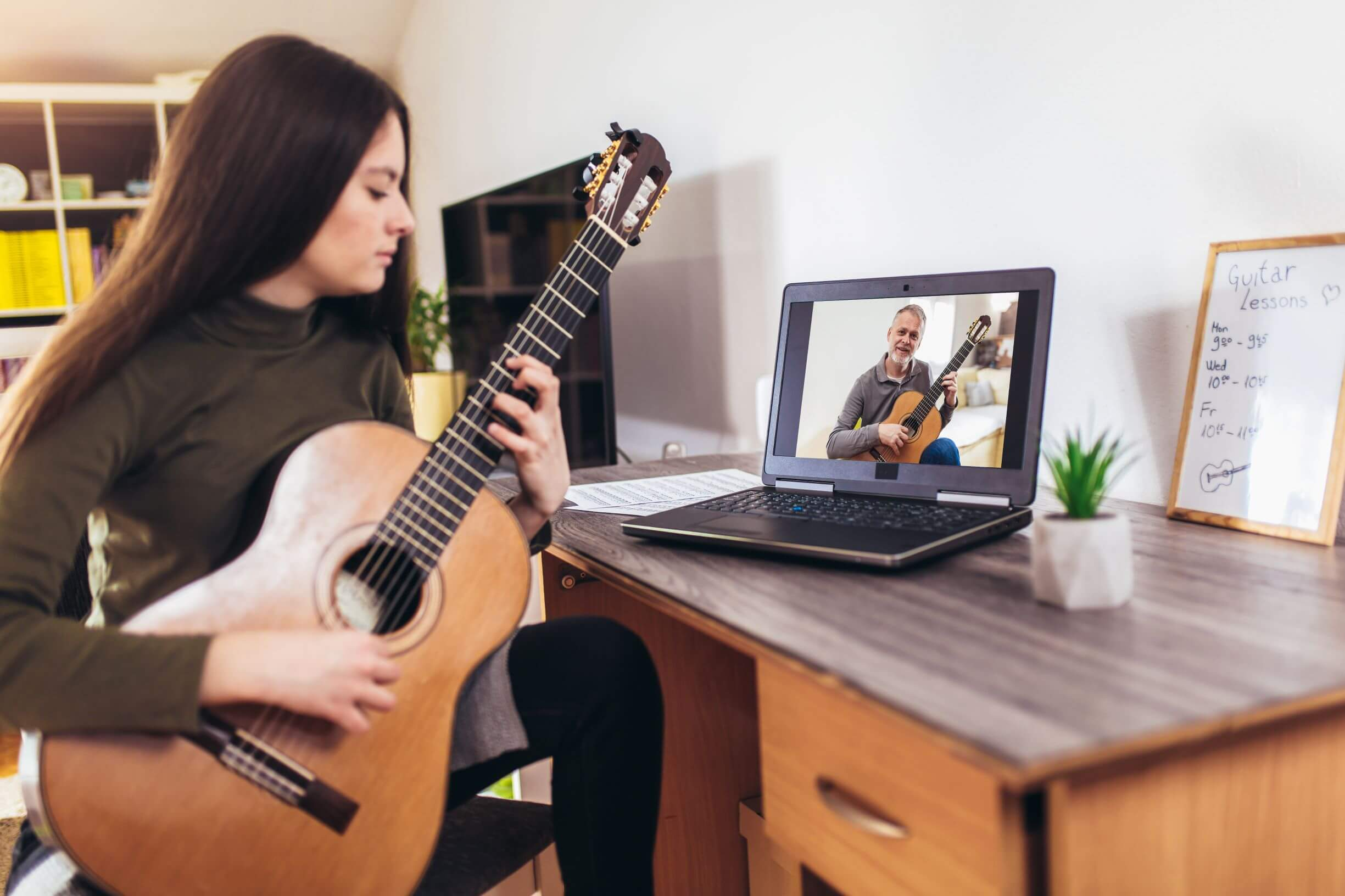 Image shows a girl learning guitar through a video.
