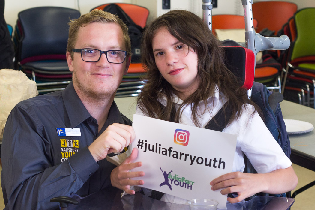 Two people holding a sign that says #JuliaFarrYouth