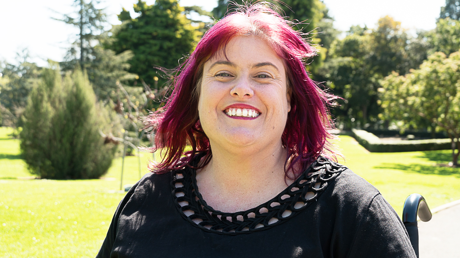 Photo of Christine Priest outside with a huge smile and purple hair