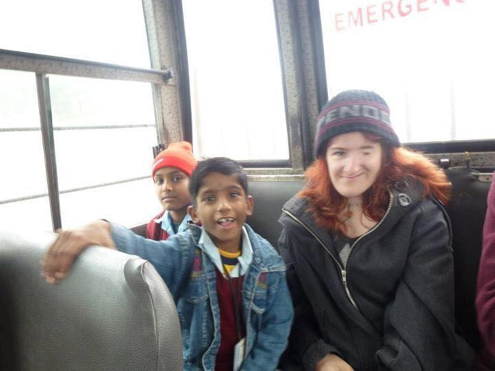 Ellen on bus with young students