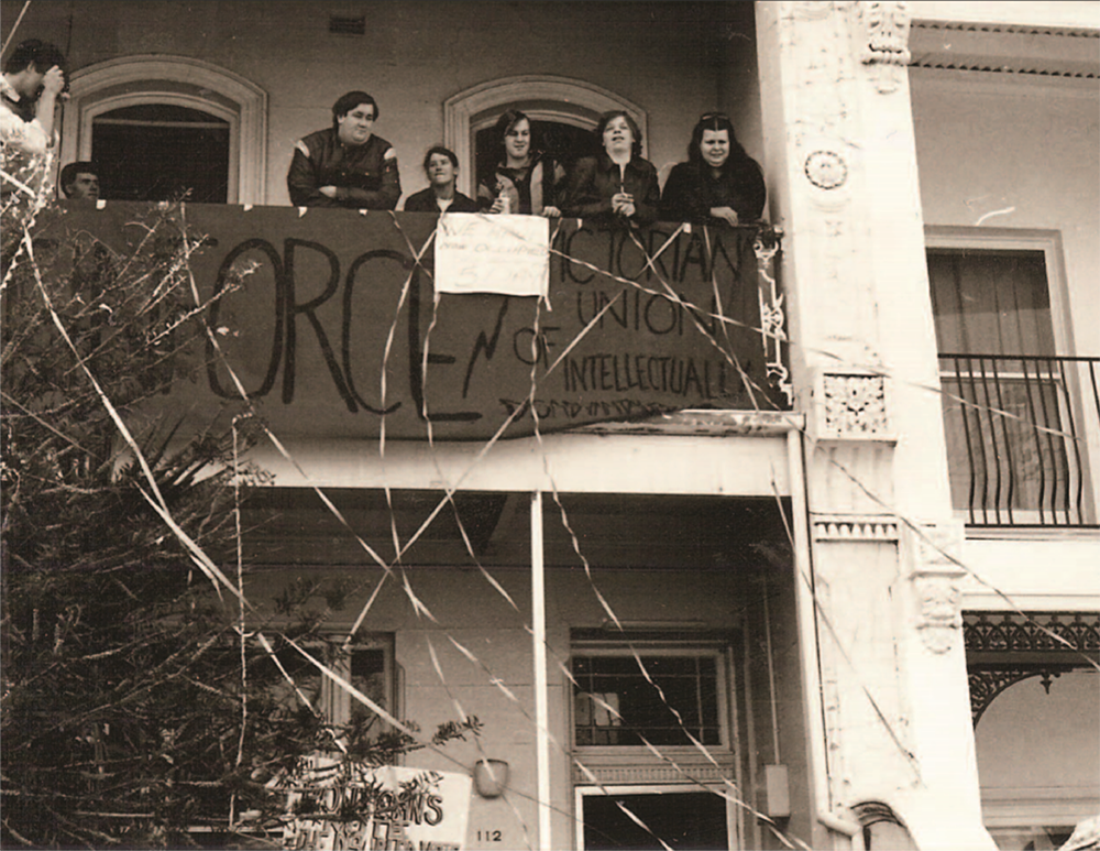 "Image is of Reinforce protesters on the top balcony of 112 Drummond Street with a sign that says: ""Reinforce: Victorian Union of Intellectual Disability"""