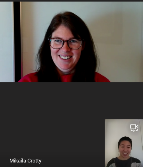 A Microsoft Teams call between Mik and Isabel. Mik is wearing glasses and a red top. Isabel is in a grey top with a striped jumper over her top and wearing earphones. Both are smiling at the camera.