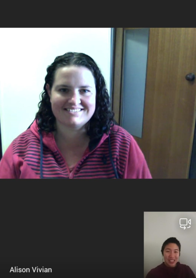 Teams call between Ali and Isabel. Ali has dark curly hair and is wearing a maroon and navy striped hoodie. Isabel is also in a maroon hoodie and has earphones in. Both are smiling at the camera.