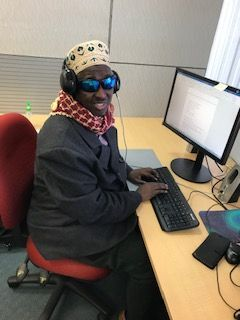 Dr Siyat takes a break from his computer at work to smile for the camera. He is wearing dark tinted glasses, dressed in a smart black blazer and wearing a scarf around his neck.