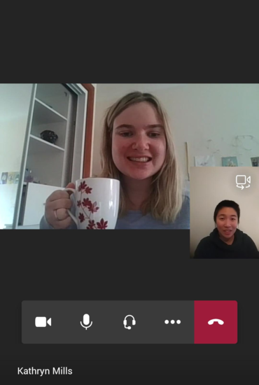 Teams call between Kathryn and Isabel. Kathryn is in a light blue top and holding up her white patterned mug. Isabel is in a dark green jumper with earphones in. Both are smiling at the camera.